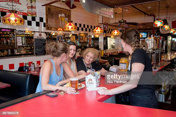 Helen Metros an 83 year old waitress at Charlie's Kitchen in Harvard Sq Cambridge MA on August 21 2013 with Alix Easton of Brighton and Nina Krane of...