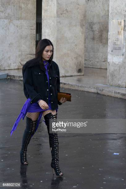 Helen Miao wears a purple dress a black coat fishnet tights and thigh high lace up boots outside the Galliano show during Paris Fashion Week...