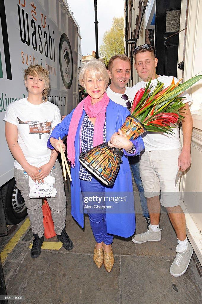 Helen Mirren is presented with flowers, a drum and an invitation to the 'As One In The Park' festival as an apology for the disruption to her stage performance on May 7, 2013 in London, England.