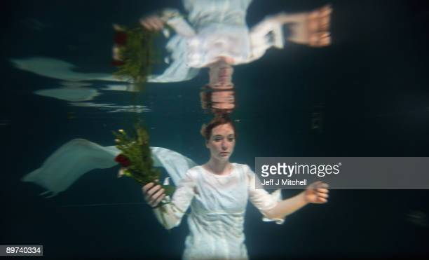 Helen Morton of the Three Bugs Fringe Theatre company performs Ophelia drowning in the Apex Hotel swimming pool during the Edinburgh Fringe Festival...