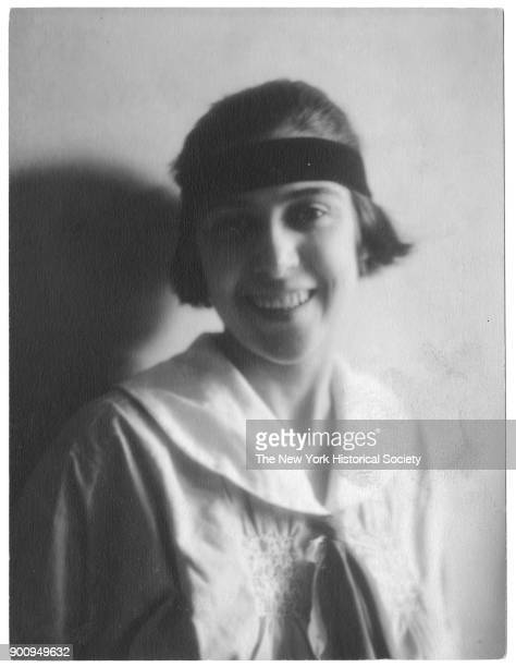 Helen Rehber with short hair headband in smocked shirt with large collar and tie as she smiles 1922