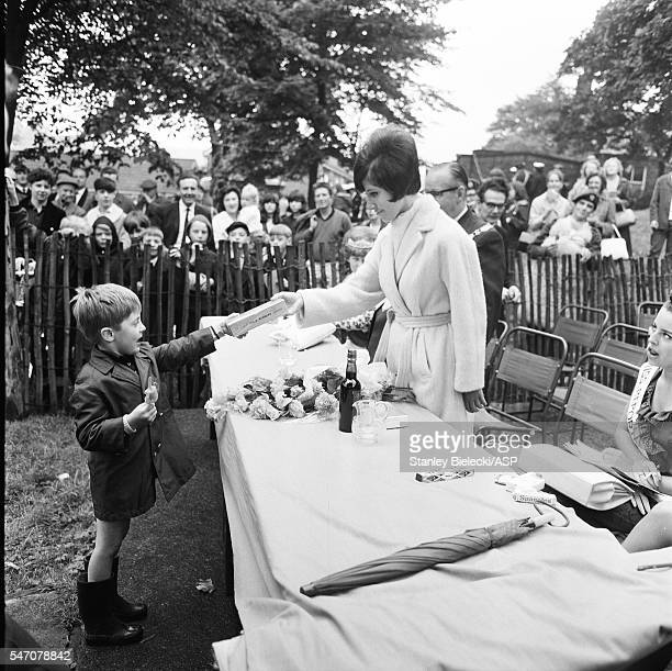 Helen Shapiro presents a box of chocolates to a young boy at a country fair in Oldham United Kingdom 1965