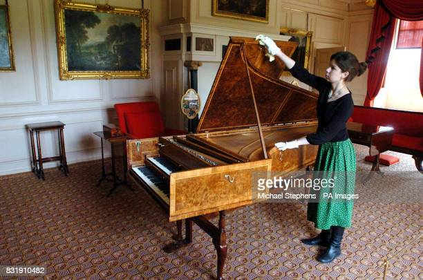 Helen Slade a member of staff at Kew Palace London holds open a harpsichord in the Queen's Drawing Room