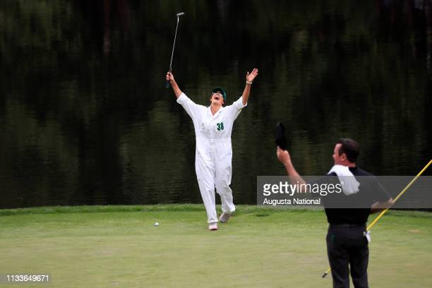 Helen Storey caddie for Lee Westwood of England celebrates after she made a putt on No 9 green during the Par 3 Contest at Augusta National Golf Club...