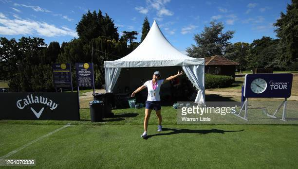 Helen Storey, fiancée and caddie of Lee Westwood of England collects practices balls on the range ahead of the English Championship at Hanbury Manor...