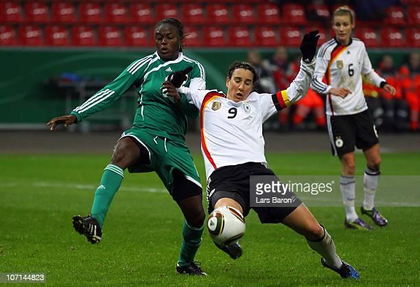Helen Ukaonu of Nigeria challenges Birgit Prinz of Germany during the women's international friendly match between Germnay and Nigeria at BayArena on...