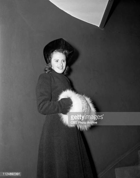 Helen Ward models a black camels wool coat and lynx cuffs as a muff, selected by fashion stylist and critic Elizabeth Hawes. Image dated: September...