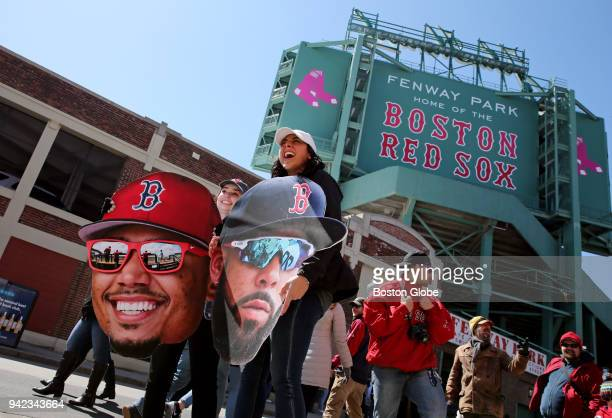 Helena Akhtar, left, and Gabrielle Onofrio carry cutouts of Mookie Betts and David Price while promoting ALT 92.9 radio outside Fenway Park before...