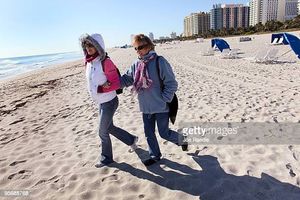 Helena Anderson and her mother Daniela Birska wear jackets as they walk on the beach on January 11 2010 in Miami Beach Florida The National Weather...