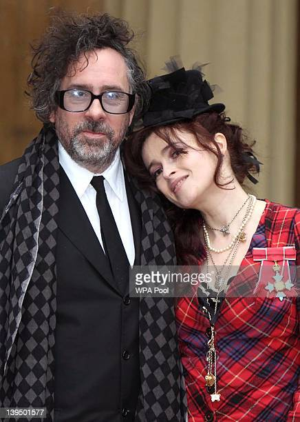 Helena Bonham Carter with her husband Tim Burton as she poses with her Commander of the British Empire medal after an Investiture ceremony at...