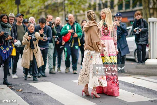 Helena Bordon and Lala Rudge pose in front of photographers outside Valentino during Paris Fashion Week Womenswear Spring/Summer 2018 on October 1...