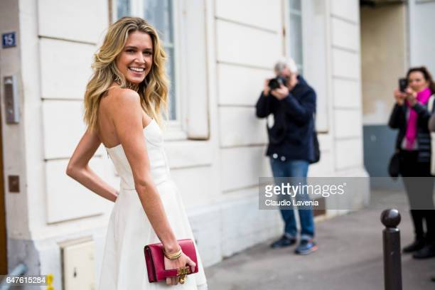 Helena Bordon is wearing a white Dior coat and a red Dior bag in the streets of Paris before the Christian Dior show during Paris Fashion Week...