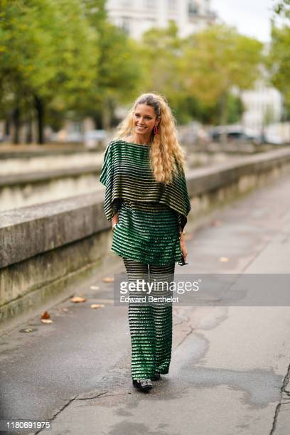 Helena Bordon wears a black and green shiny glitter striped outfit flare pants outside Valentino during Paris Fashion Week Womenswear Spring Summer...