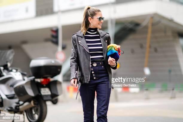 Helena Bordon wears a black leather jacket a striped top blue pants white shoes outside Giambattista Valli during Paris Fashion Week Womenswear...