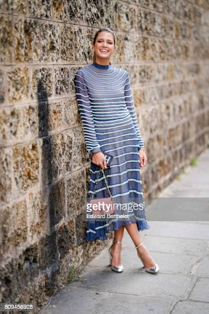 Helena Bordon wears a blue lace striped dress a pink bag and heels outside the Valentino show during Paris Fashion Week Haute Couture Fall/Winter...