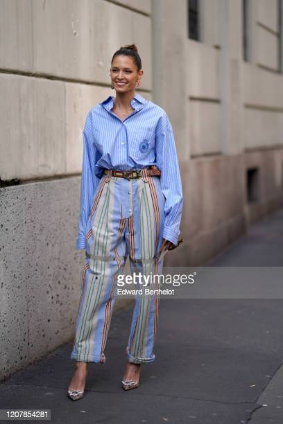 Helena Bordon wears a blue oversized striped shirt, a belt, cropped flared colored striped pants, earrings, outside Etro, during Milan Fashion Week...