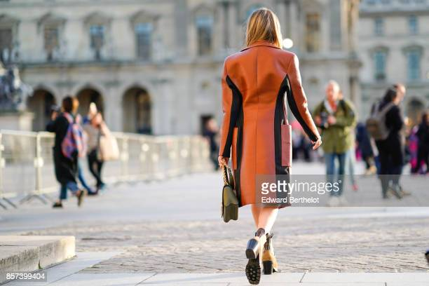 Helena Bordon wears a brown leather coat a white dress outside Louis Vuitton during Paris Fashion Week Womenswear Spring/Summer 2018 on October 3...