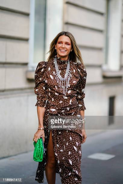 Helena Bordon wears a brown lustrous dress with printed features including polka dots, a bejeweled necklace, a green bag, outside Alessandra Rich,...