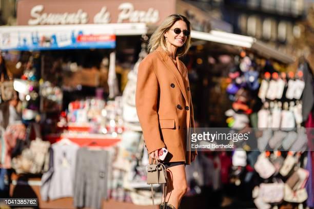 Helena Bordon wears a brown oversized blazer jacket high boots outside Rochas during Paris Fashion Week Womenswear Spring/Summer 2019 on September 26...