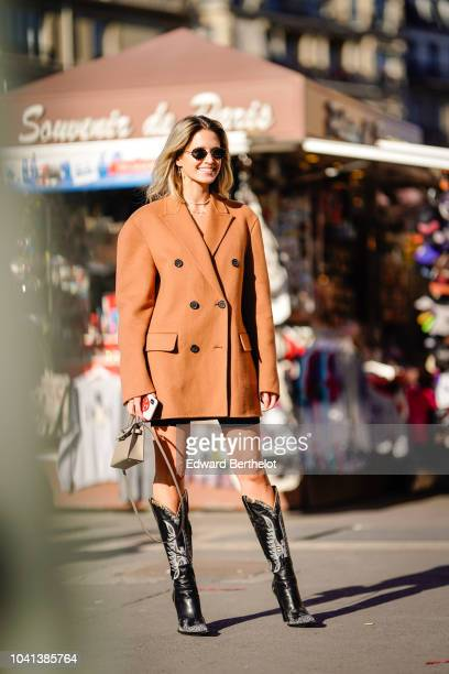 Helena Bordon wears a brown oversized blazer jacket high boots outside Rochas during Paris Fashion Week Womenswear Spring/Summer 2019 on September 26...
