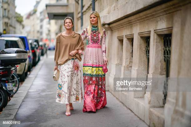 Helena Bordon wears a camel top a white flower print skirt Lala Rudge wears a pink flower print dress outside Valentino during Paris Fashion Week...