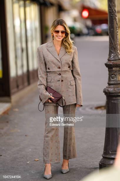 Helena Bordon wears a checked blazer jacket flare pants a bag outside Altuzarra during Paris Fashion Week Womenswear Spring/Summer 2019 on September...