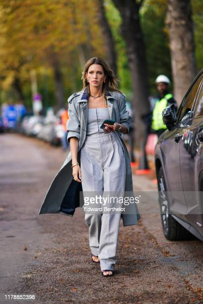 Helena Bordon wears a gray trench coat, a gray off-shoulder top, flare pants, outside Lacoste, during Paris Fashion Week - Womenswear Spring Summer...