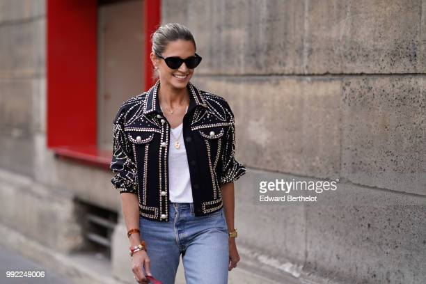 Helena Bordon wears a jacket with shiny embroidery a white top ripped jeans a bag outside Elie Saab during Paris Fashion Week Haute Couture Fall...