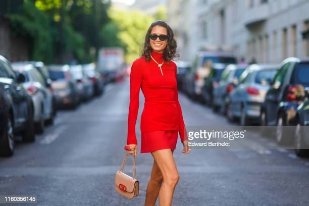 Helena Bordon wears a red dress a necklace a Valentino bag red shoes outside Valentino during Paris Fashion Week Haute Couture Fall/Winter 2019/2020...