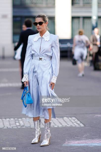 Helena Bordon wears a white and blue dress with a shirt collar a blue bag silver shiny boots sunglasses outside Fendi during Paris Fashion Week Haute...