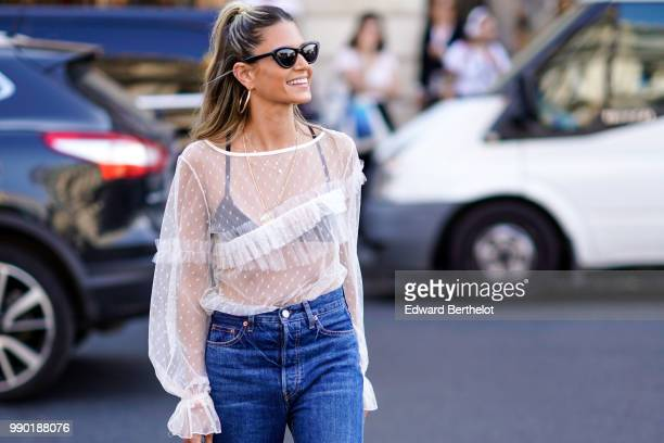 Helena Bordon wears a white lace mesh top blue jeans pink shoes outside Schiaparelli during Paris Fashion Week Haute Couture Fall Winter 2018/2019 on...