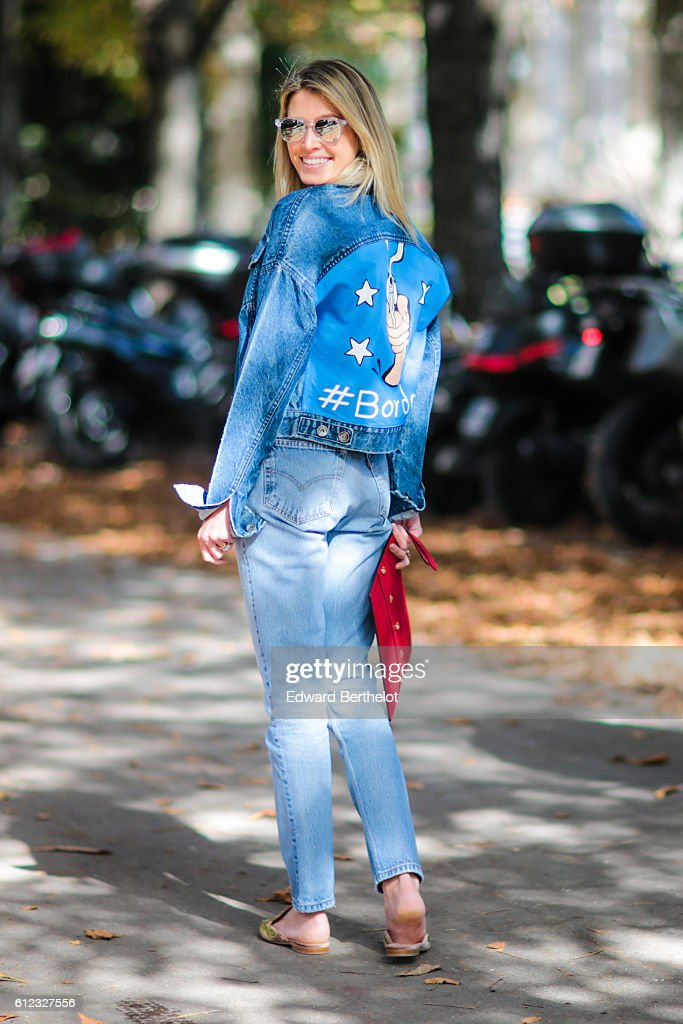 Helena Bordon wears blue denim jeans, a blue denim jacket with her name written on the back, a red clutch, and sunglasses, outside of the Giambattista Valli show during Paris Fashion Week Spring Summer 2017, at Grand Palais, on October 3, 2016 in Paris, France.