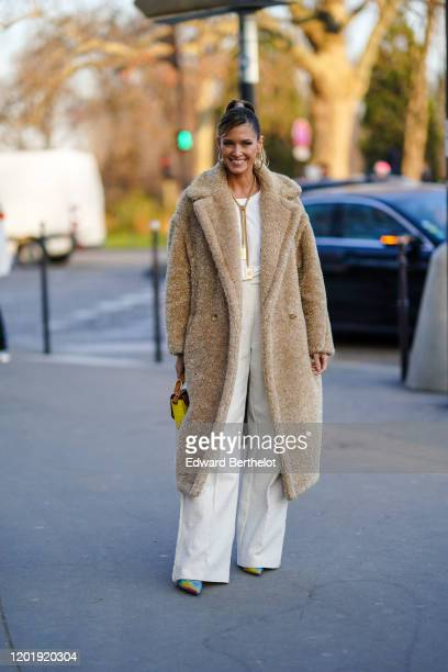 Helena Bordon wears earrings, a Chanel necklace, a glittering beige fluffy coat, a white top, white wide-legs full-length pants, a yellow and brown...