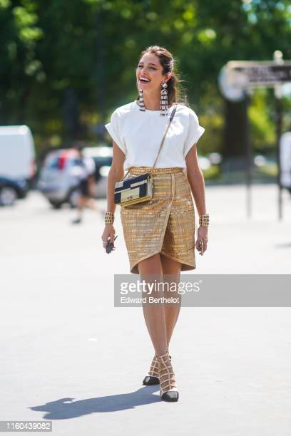 Helena Bordon wears long earrings, a white t-shirt, a golden skirt, shoes, a golden Chanel bag, outside Chanel, during Paris Fashion Week -Haute...