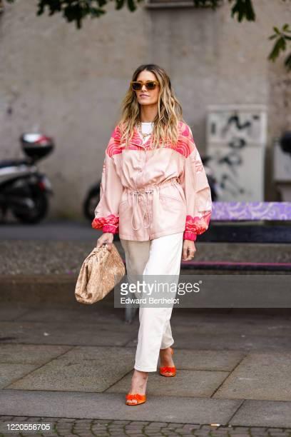 Helena Bordon wears sunglasses, a pink jacket, white pants, a Pouch Bottega Veneta bag, orange shoes, outside Koche x Pucci, during Milan Fashion...