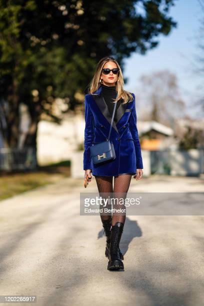 Helena Bordon wears sunglasses, earrings, a blue long jacket/dress, a turtleneck top, a Hermes bag, fishnet tights, black long leather boots, outside...