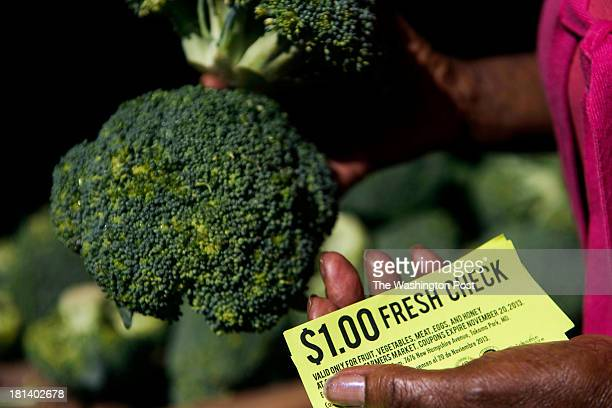 Helena Cumberbatch uses a Fresh Check to purchase her produce at the Crossroads Farmers' market on Wednesday, Sept. 4, 2013 in Takoma Park, MD. The...