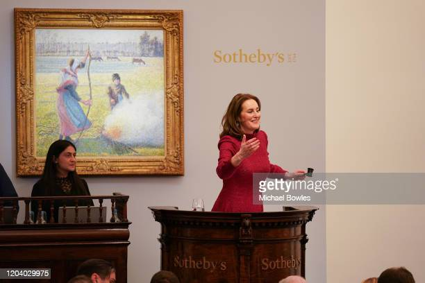 Helena Newman, Sotheby's European Chairman fields bids during the sale of Camille Pissarro's 'Gelée blanche, jeune paysanne faisant du feu', which...