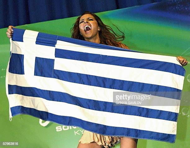 Helena Paparaizou of Greece winner of 50th Eurovision Song Contest dances on a table with National flag during a press conference in Kiev 22 May 2005...