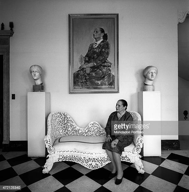 """""""Helena Rubinstein, in her wealthy house, sits on a canap made of carved and pierced stone, between two Roman heads and under her own portrait..."""