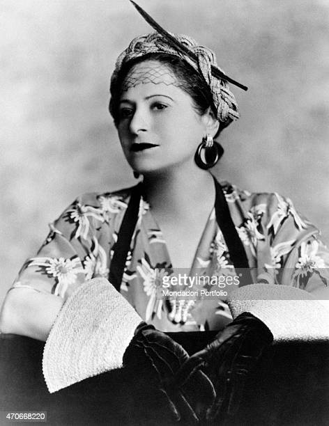 'Helena Rubinstein portrayed on a photo studio with a fancy American dress the Polish born American entrepreneur wears a braided rope crown a pair of...