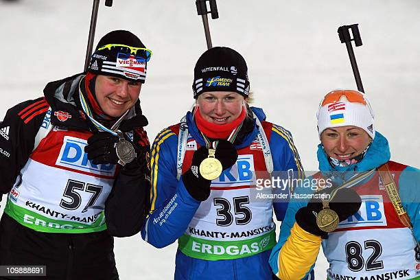 Helene Ekholm of Sweden poses with Tina Bachmann of Germany and Vita Semerenko of Ukraine at the medal ceremony for the women's 15km individual race...