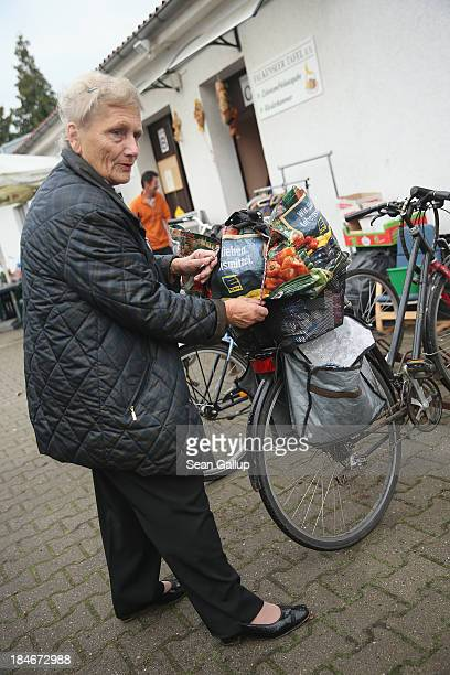 Helga who survives on a monthly pension of EUR 520 and who has been coming to the food bank for about a year prepares to depart on her bicycle after...