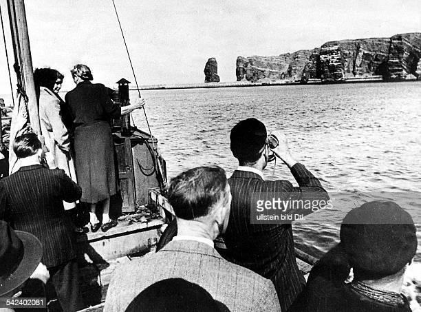 Helgoländer die zum ersten Male nach fast 6 Jahren ihre Heimat wiedersehen sie fahren um die Insel herum hinten die Felsformation Hengst September...