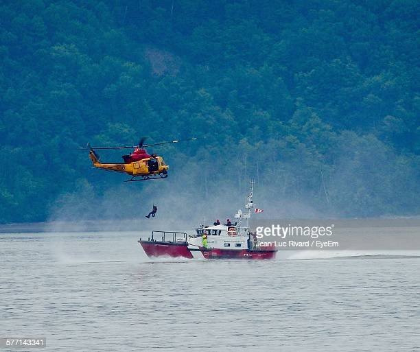 helicopter above coast guard boat - rescue worker stock pictures, royalty-free photos & images