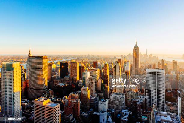 helicopter aerial view of new york city skyline during sunset, ny, united states - new york city stock-fotos und bilder