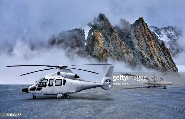 helicopter and propeller airplane on parking apron at snow-capped mountains backgrounds - european alps stock pictures, royalty-free photos & images