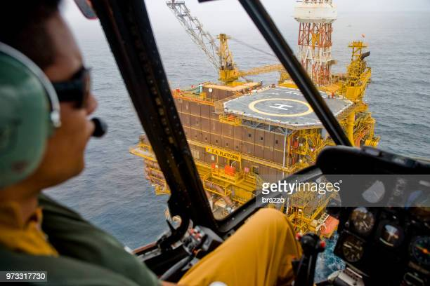 helicopter approaches a drilling rig - sikorsky helicopter stock pictures, royalty-free photos & images