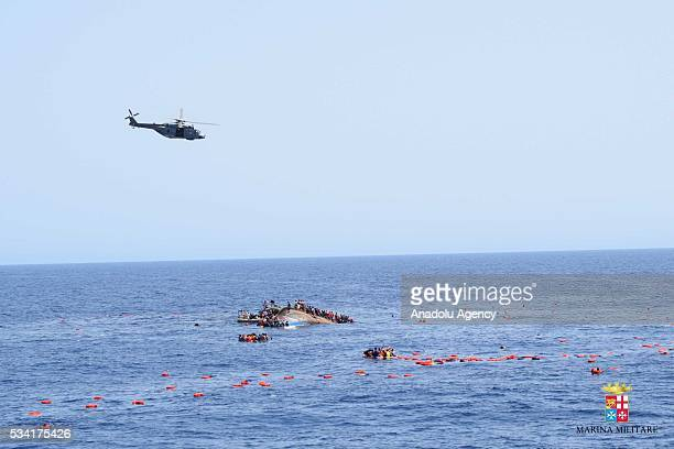 A helicopter approaches to the capsized boat as Italian marines rescue migrants from an overcrowded boat at Sicilian Strait between Libya and Italy...