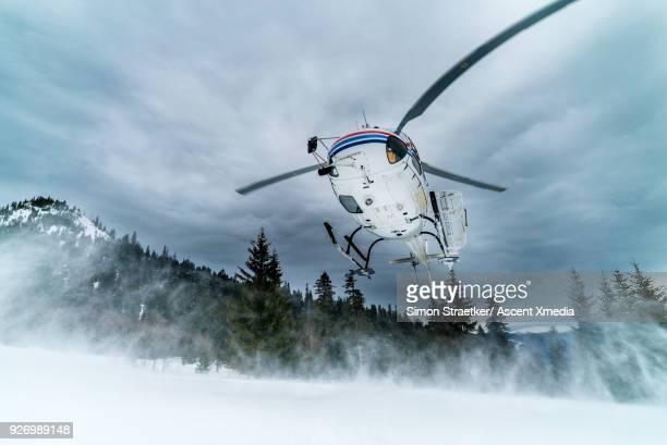 helicopter arrives on snow crest with heli-skiers - kaukasus geografische lage stock-fotos und bilder
